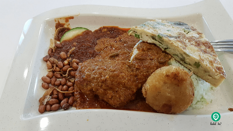 That's butter chicken and bergedil (fried potato patties) to complete a customer's meal of Nasi Lemak at PwC Cafeteria. Singapore